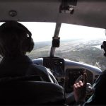 Flight instructor raising index finger while student trains in aircraft.